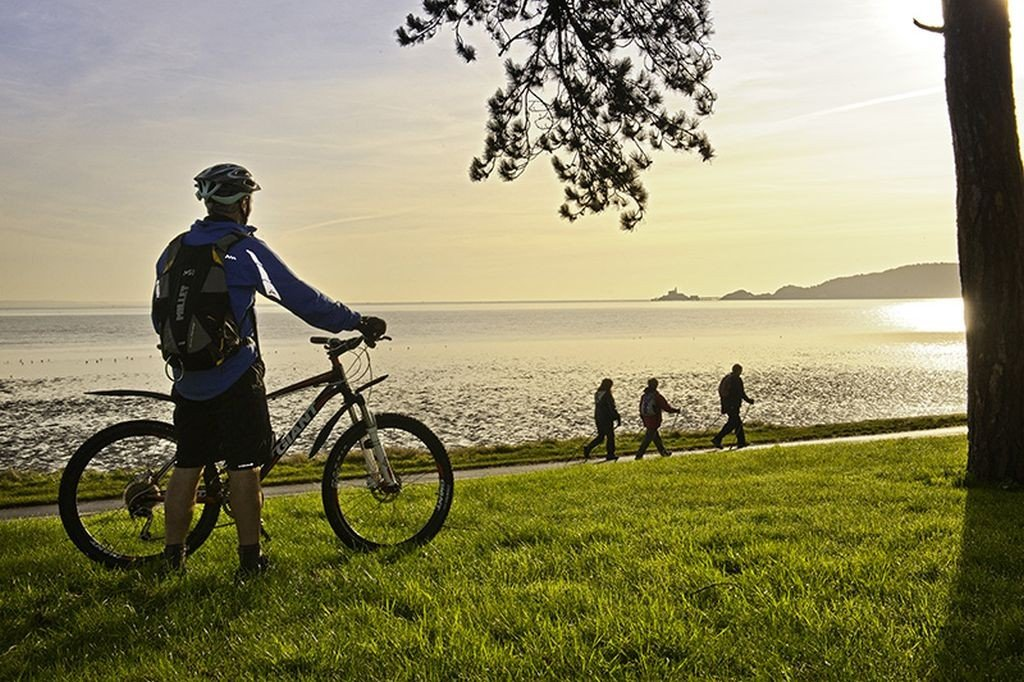 Cyclists on Coast Path at Blackpill at sunrise with Mumbles Head in background. Swansea South Cycling