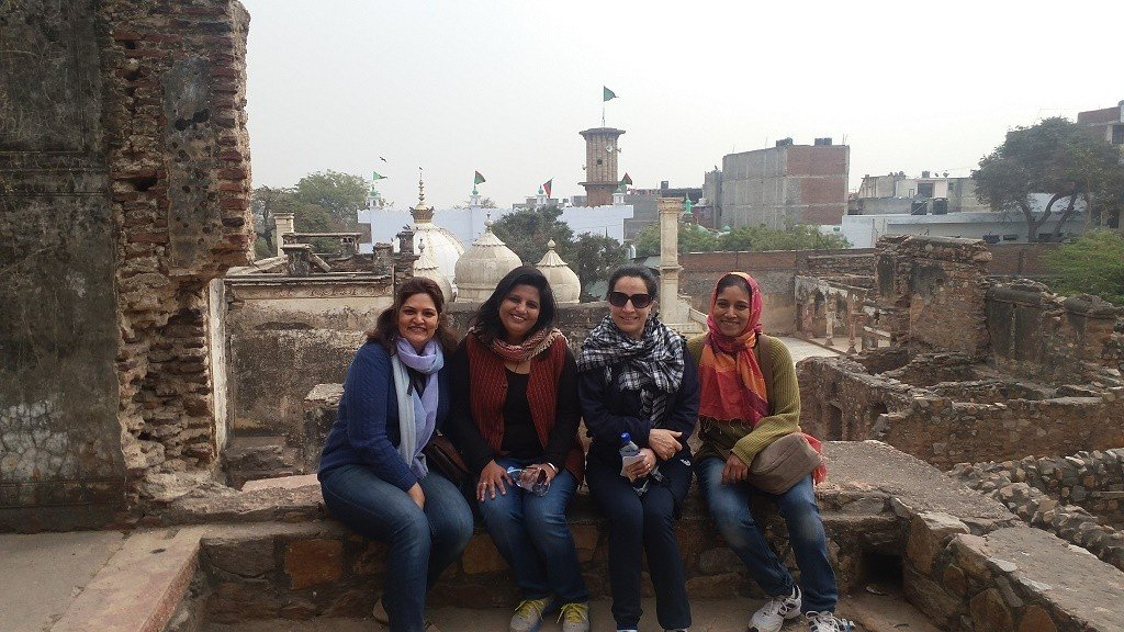 women inside the crumbling remains of Zafar Mahal with Moti Masjid in the background. Photo: Vaydehi K.