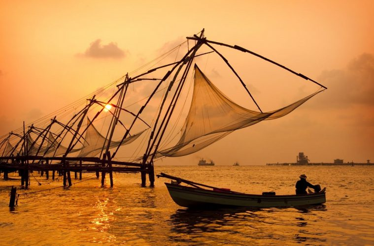 Sunset over Chinese fishing nets and boat in cochin kochi , kerala, india
