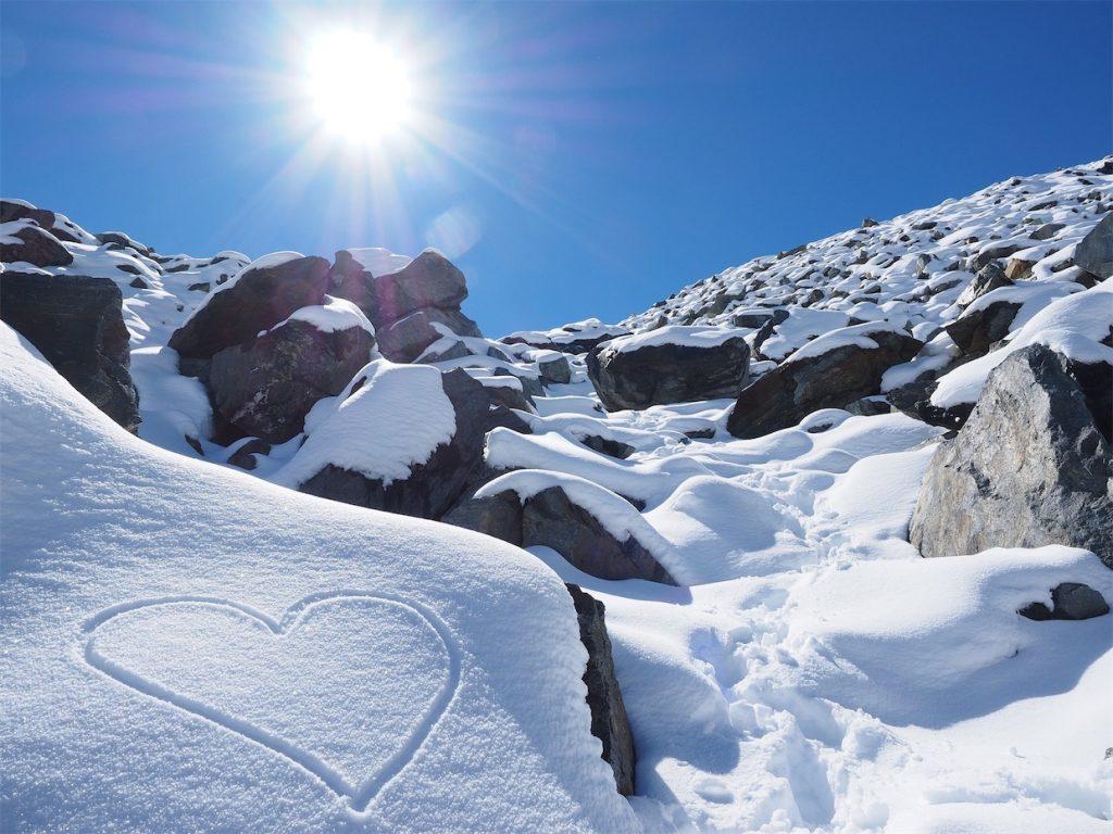 green date Heart on snowy mountain