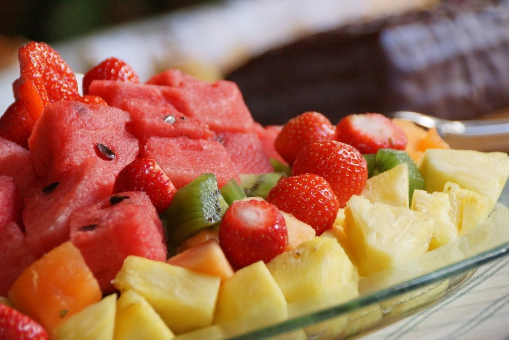 Fruit bowl with watermelon, strawberries, kiwi, pineapple, and cantaloupe wellness tips