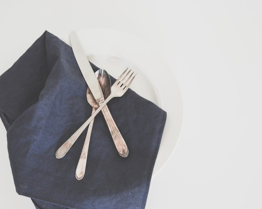 Silverware utensils on a navy blue napkin