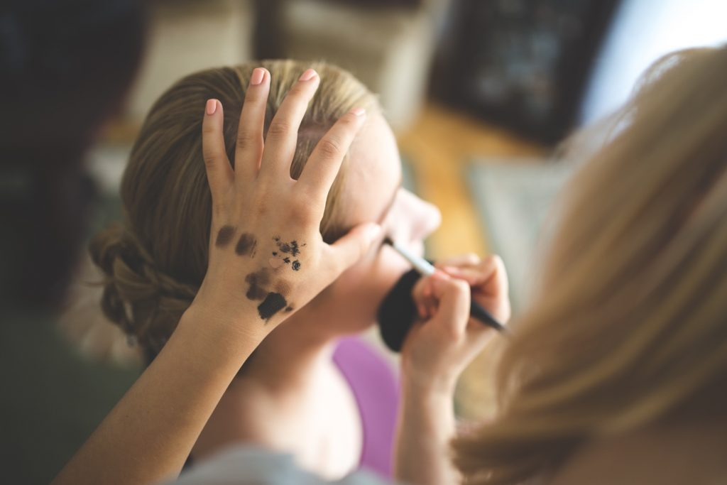 Woman applying eyeliner to another woman's face