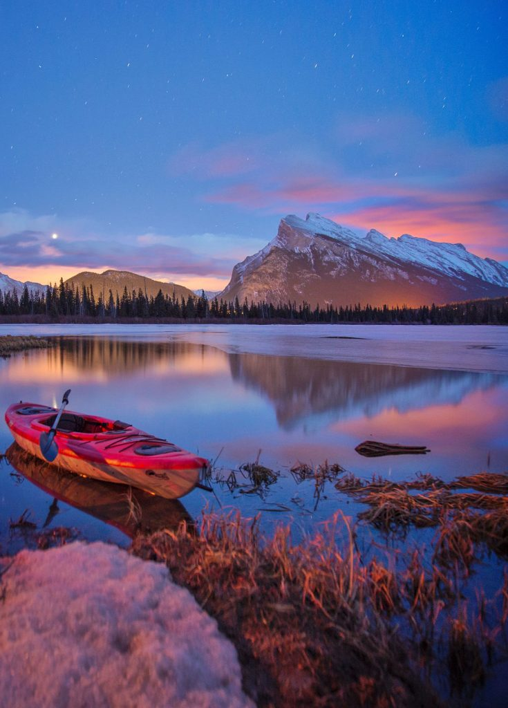 Vermillion Lakes lit by Banff's ambient light with kayak