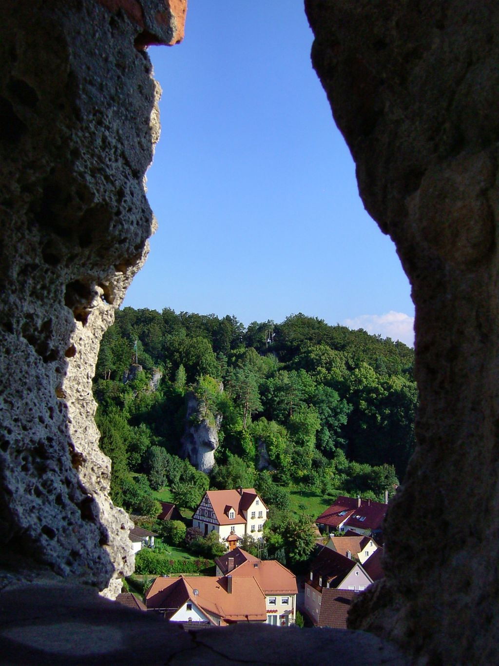 Frankenjura Germany view out of the bottom of a gorge looking over a small town in the trees. jaw-dropping rock climbing gorge