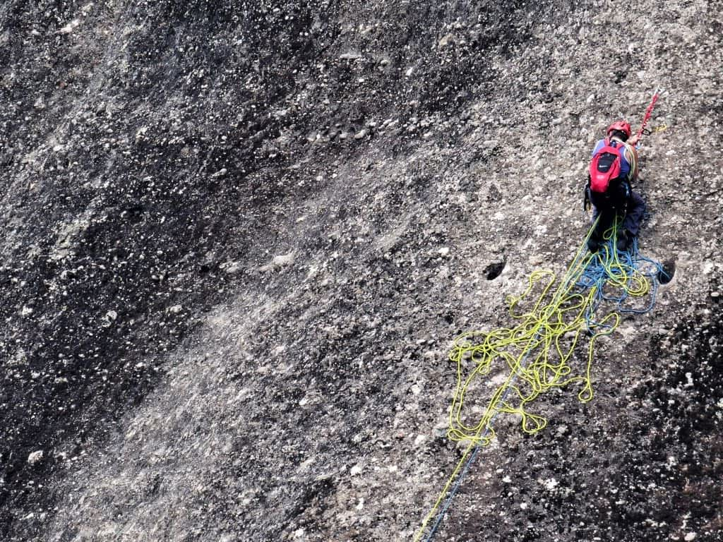 Rock climber on juggy wall pulling slack for cleaning climber below