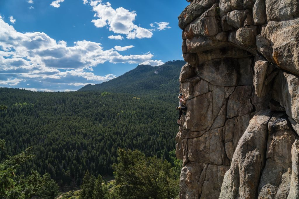 photo on middle of cliff face over looking the forest woman rock climbing