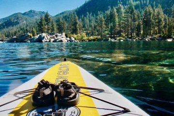 view from paddle board crystal clear water mountain in background