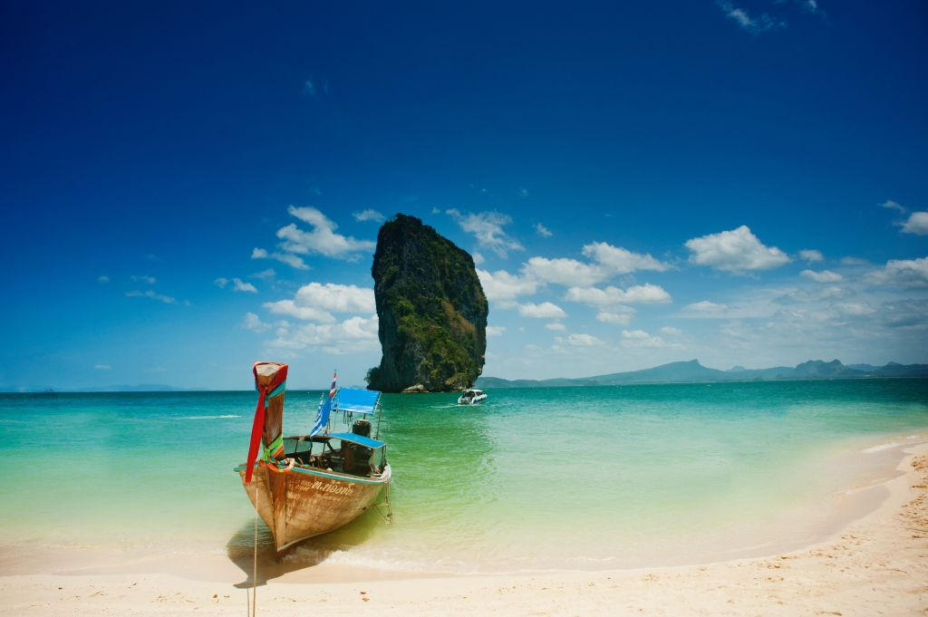 long boat tied off to white shore beach and clear blue water leads to pillar like rock formation with greenery. jaw-dropping rock climbing location