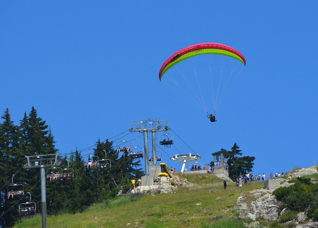 British Columbia or BC canada. a paraglider taking off near a ski lift that brought them up