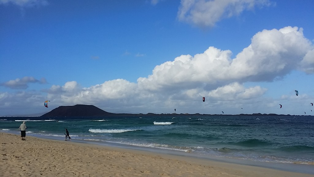 Photo taken from the beach of a few kite surfers out on the water.
