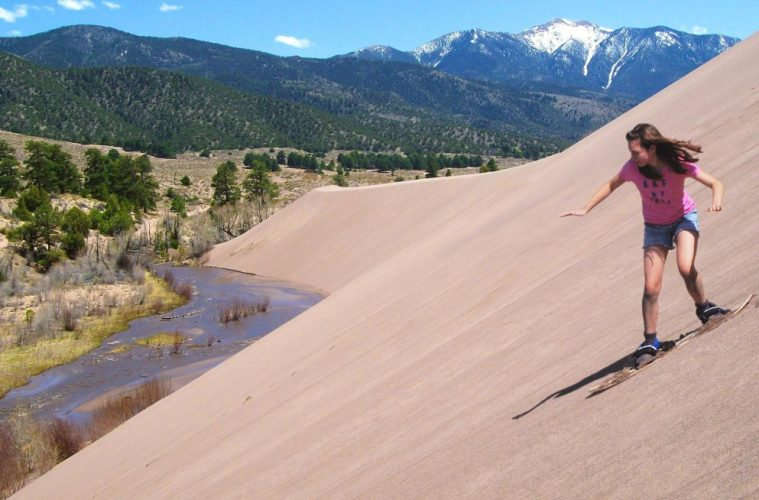 Girl Sandboarding Above Medano Creek, Great Sand Dunes National Park, Colorado