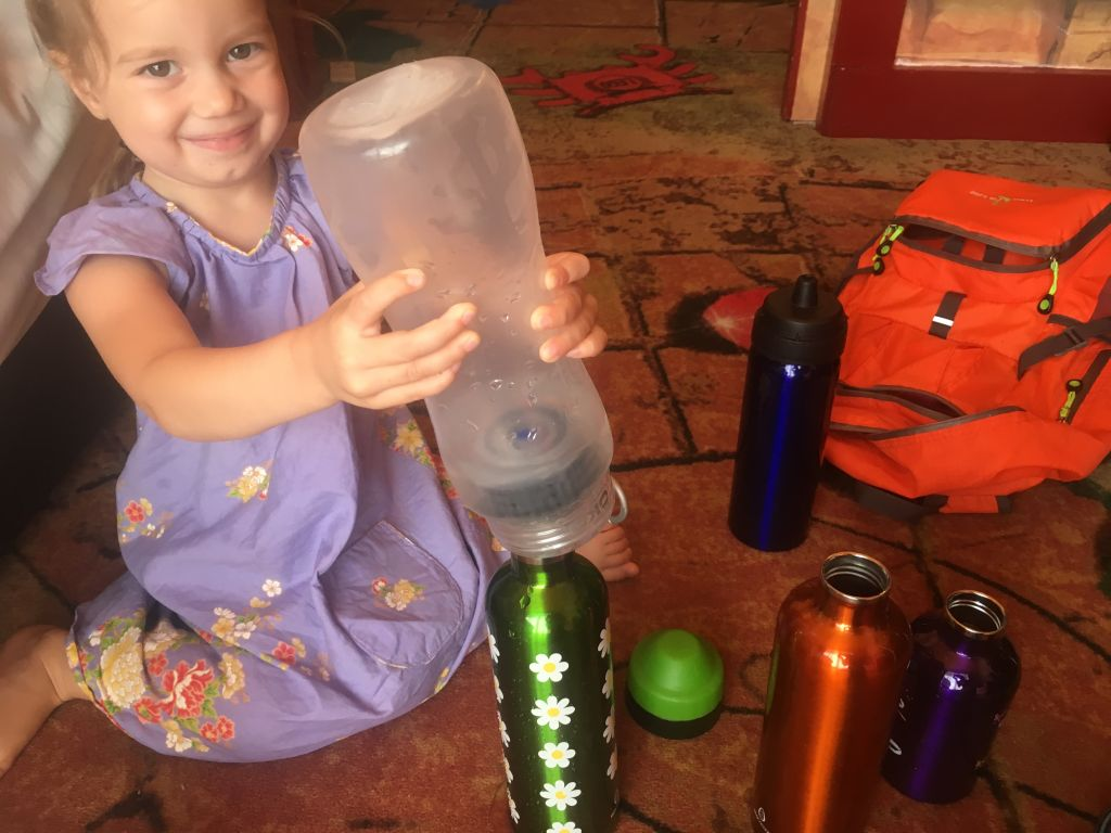 Zero waste/low waste travel bring your own water bottle small child filling a reusable water bottle with a water filtering water bottle