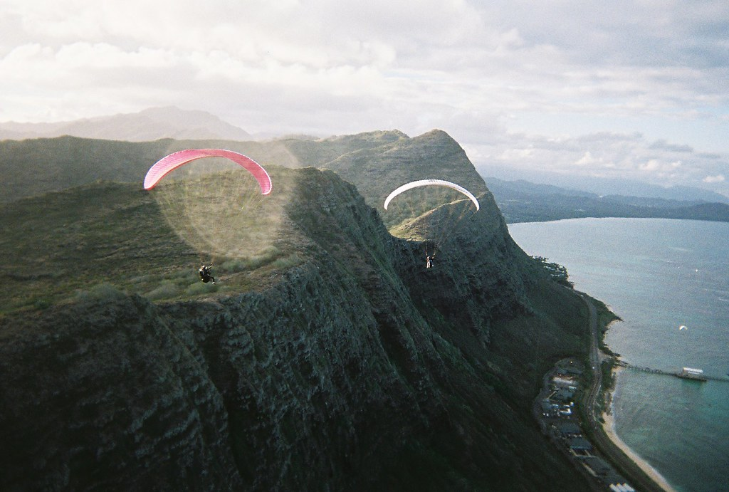 two paragliders in front of huge cliffs covered in small greenery