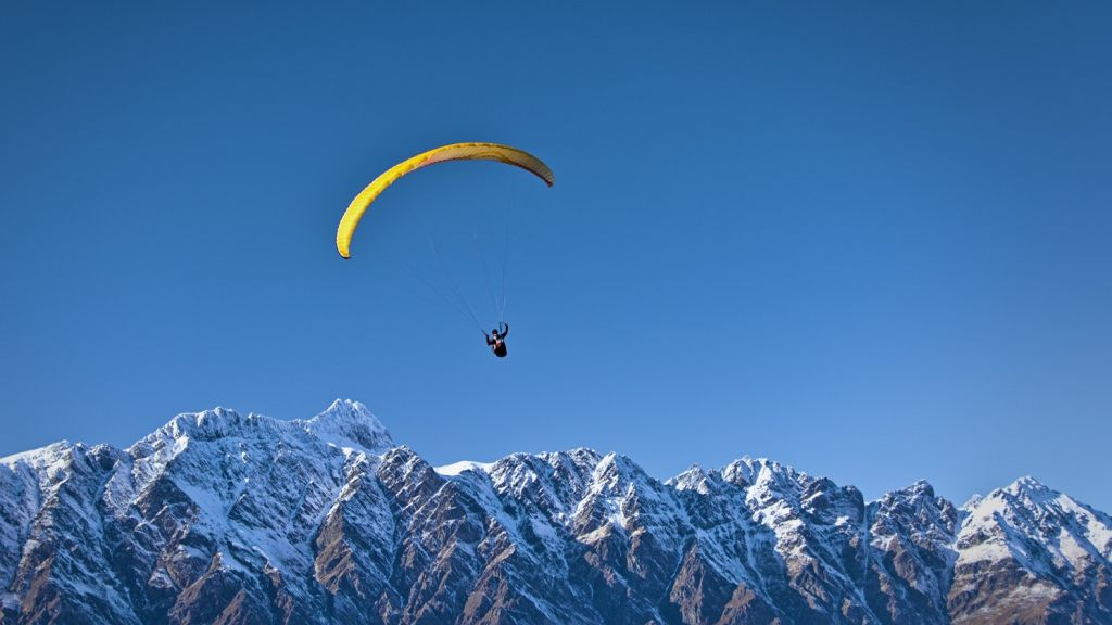 Paragliding in front of a snow capped mountain ridge