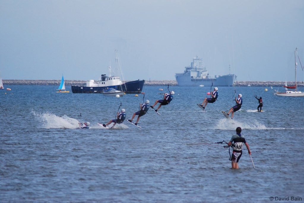 an overlap photo of a kite surfer jumping so it shows different points of the jump overlapped