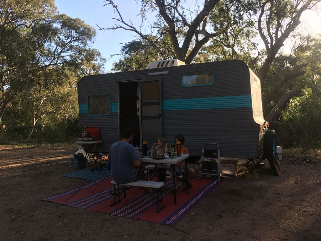 camper with small table and family eating a sustainable meal