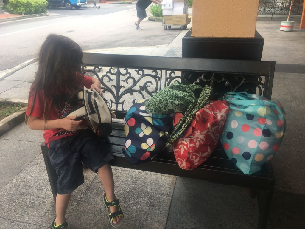 child sitting on bench next to resuable shopping bags