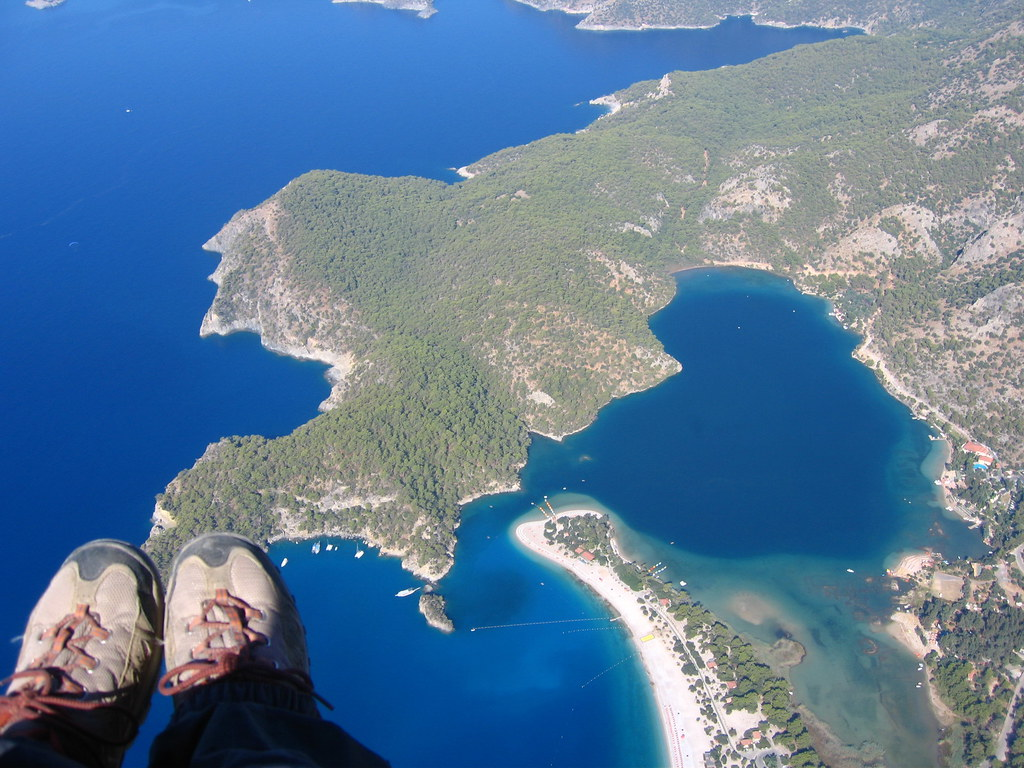 two feet at the corner of an in flight paraglide over a blue bay and white sand beach.