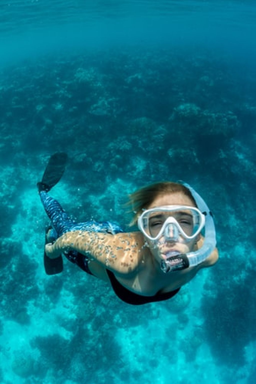 Woman free diving wearing snorkel and fins underwater with reef in background