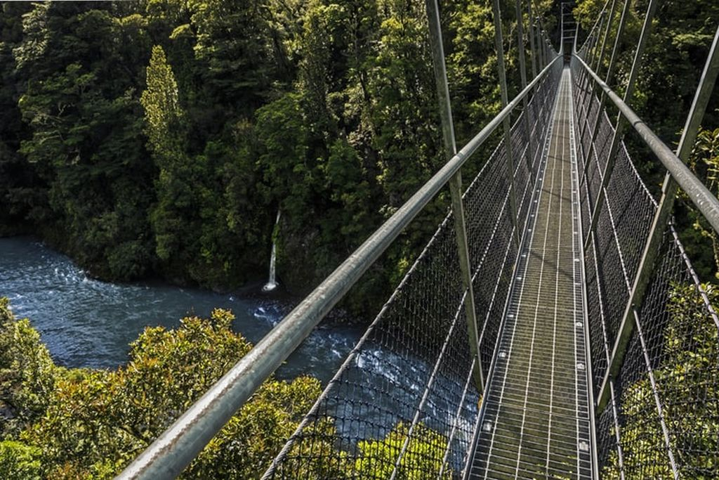 suspension bridge over a gushing river going from one side with lush forest to the other