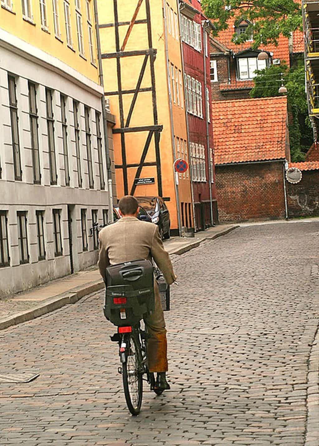 bike cobblestone street passing Swedish buildings